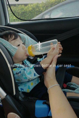 finally holding own bottle in car seat